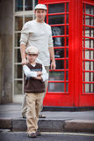 Happy father and son outdoors by red phone booth Royalty Free Stock Photo