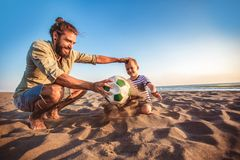 Happy father and son play soccer or football on the beach royalty free stock images