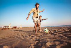 Happy father and son play soccer or football on the beach royalty free stock photo