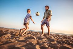 Happy father and son play soccer or football on the beach stock image