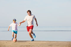 Happy father and son play soccer or football on Stock Photos