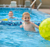 Happy father and son playing with ball in swimming pool Royalty Free Stock Image
