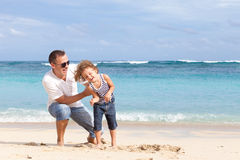Happy father and son playing on the beach at the day time. Royalty Free Stock Photography
