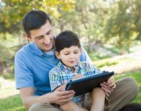 Happy Father and Son Playing on a Computer Tablet Outside. Happy Father with His Son Playing on a Computer Tablet Outside royalty free stock photo