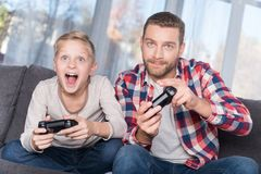 Father and son playing with joysticks Stock Photos