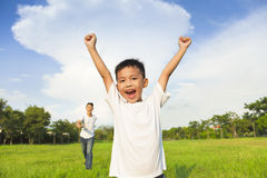 Happy father and son playing in meadow. With sky background Royalty Free Stock Image
