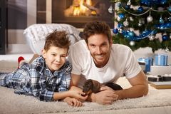 Happy father and son playing with puppy at xmas. Happy young father and son lying on floor at christmas time, playing with adorable dachshund puppy received for Royalty Free Stock Image