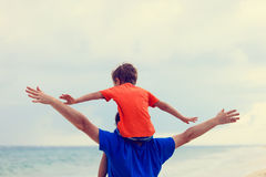 Happy father and son playing on sea beach Royalty Free Stock Images