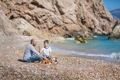Happy father and son playing together at beach Stock Photography