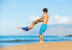 Happy father and son playing together at beach Stock Photo