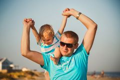 Happy father and son playing together at beach. Father is holding his son at shoulders.  Royalty Free Stock Photos