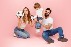 Happy father and son playing together with soccer ball on pink royalty free stock photos