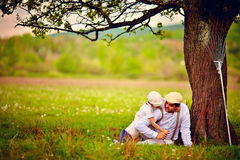 Happy father and son playing together under an old tree Stock Image