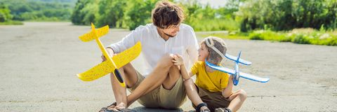 Happy father and son playing with toy airplane against old runway background. Traveling with kids concept BANNER, LONG. Happy father and son playing with toy royalty free stock photo