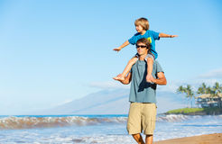 Happy father and son playing on tropical beach, carefree happy f Royalty Free Stock Photo