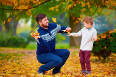 Happy father and son playing in vibrant autumn park Royalty Free Stock Photography