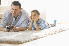 Happy father and son playing video game on floor at home Stock Images