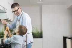 Happy father and son preparing spaghetti in kitchen Stock Image