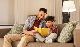 Happy father and son reading book sofa at home. Family, childhood, fatherhood, leisure and people concept - happy smiling father and little son reading book on stock image