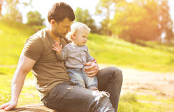 Happy father and son resting sitting on grass summer Stock Photos