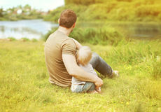 Happy father and son resting sitting together on grass summer royalty free stock image