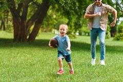happy father and son running with american football ball