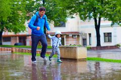 Happy father and son running under the rain Stock Images