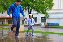 Happy father and son running under the rain Royalty Free Stock Photos