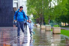 Happy father and son running under the rain Royalty Free Stock Photography