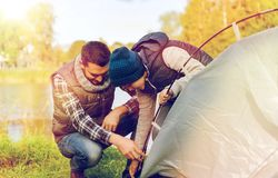 Happy father and son setting up tent outdoors. Camping, tourism, hike, family and people concept - happy father and son setting up tent outdoors Royalty Free Stock Photography