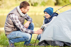 Happy father and son setting up tent outdoors. Camping, tourism, hike, family and people concept - happy father and son setting up tent outdoors Stock Images