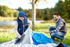 Happy father and son setting up tent outdoors Royalty Free Stock Photos