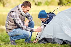 Happy father and son setting up tent outdoors Royalty Free Stock Photo