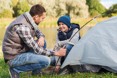Happy father and son setting up tent outdoors. Camping, tourism, hike, family and people concept - happy father and son setting up tent outdoors Royalty Free Stock Images