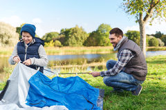 Happy father and son setting up tent outdoors. Camping, tourism, hike, family and people concept - happy father and son setting up tent outdoors Royalty Free Stock Photo