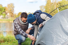 Happy father and son setting up tent outdoors. Camping, tourism, hike, family and people concept - happy father and son setting up tent outdoors Royalty Free Stock Image