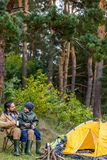 Father and son in camping. Happy father and son sitting in camping with tent in forest Royalty Free Stock Photography