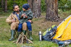Father and son in camping with tent. Happy father and son sitting in camping with tent in forest Royalty Free Stock Photo