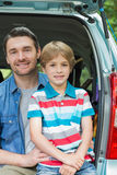 Happy father and son sitting in car trunk Royalty Free Stock Photo