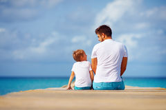 Happy father and son sitting on pier and talk Stock Images
