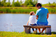 Happy father and son sitting on the river bank Royalty Free Stock Images