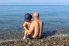 Happy father and son sitting on the seaside Royalty Free Stock Image