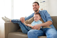 Happy father and son sitting on sofa at home. Family, childhood, fatherhood and people concept - happy father and little son sitting on sofa at home Royalty Free Stock Photo