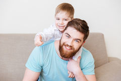 Happy father and son sitting on sofa at home together. Portrait of happy father and son sitting on sofa at home together royalty free stock images