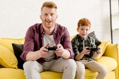 Happy father and son sitting on sofa and playing with joysticks. At home royalty free stock photos