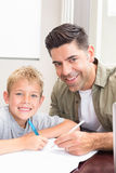Happy father and son sitting at table colouring together. At home in kitchen Royalty Free Stock Image