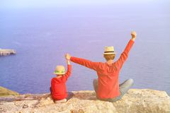Happy father and son sitting on top of a mountain. Father and son sitting on top of a mountain expressing joy with their arms stretched up towards sky Royalty Free Stock Image