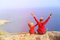Happy father and son sitting on top of a mountain. Father and son sitting on top of a mountain expressing joy with their arms stretched up towards sky Stock Images
