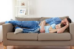 Happy father and son sleeping on sofa at home. Family, childhood, fatherhood, leisure and people concept - portrait of happy father and little son sleeping on Stock Image