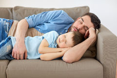 Happy father and son sleeping on sofa at home. Family, childhood, fatherhood, leisure and people concept - portrait of happy father and little son sleeping on Royalty Free Stock Photography